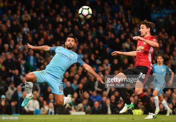 Manchester City's Argentinian striker Sergio Aguero eyes the ball as Manchester United's Italian defender Matteo Darmian defends during the English...