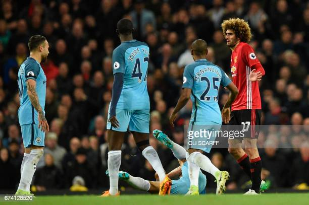 Manchester City's Argentinian striker Sergio Aguero goes down after an altercation with Manchester United's Belgian midfielder Marouane Fellaini...