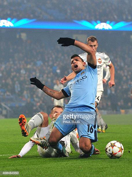Manchester City's Argentinian striker Sergio Aguero is challenged by CSKA Moscow's defender Sergey Ignashevich before he was shown the yellow card...