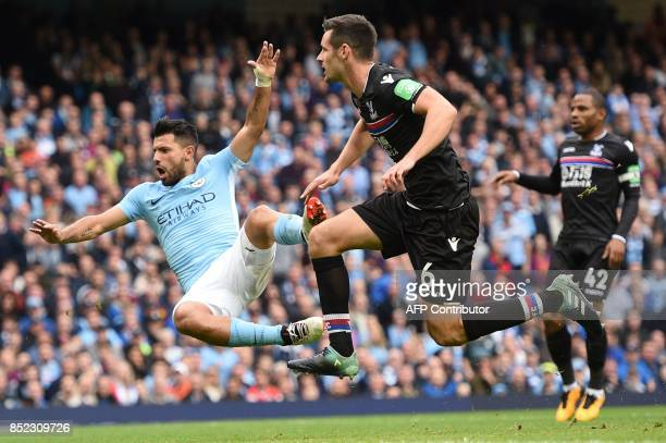 Manchester City's Argentinian striker Sergio Aguero is challenged by Crystal Palace's English defender Scott Dann during the English Premier League...