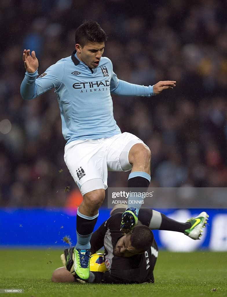 """Manchester City's Argentinian striker Sergio Aguero (C) jumps over Reading's Australian goalkeeper Adam Federici (bottom) during the Premiership football match between Manchester City and Reading at The Etihad stadium in Manchester, northwest of England on December 22, 2012. AFP PHOTO / ADRIAN DENNIS RESTRICTED TO EDITORIAL USE. No use with unauthorized audio, video, data, fixture lists, club/league logos or """"live"""" services. Online in-match use limited to 45 images, no video emulation. No use in betting, games or single club/league/player publications."""