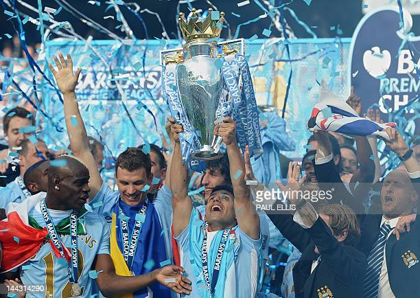 Manchester City's Argentinian striker Sergio Aguero lifts the Premier league trophy after their 32 victory over Queens Park Rangers in the English...