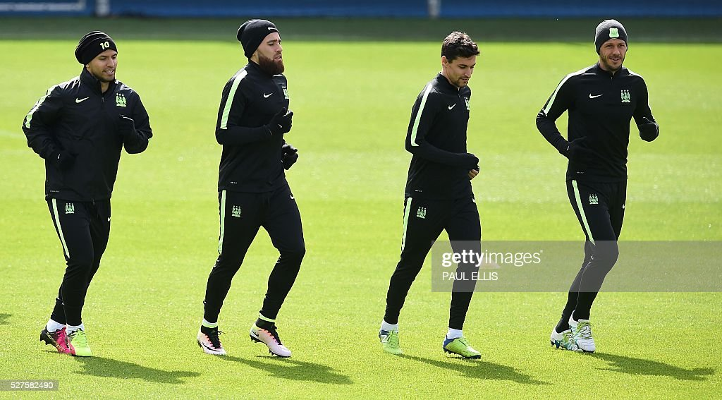 Manchester City's Argentinian striker Sergio Aguero (L) Manchester City's Argentinian defender Nicolas Otamendi (2L) Manchester City's Spanish midfielder Jesus Navas (2R) and Manchester City's Argentinian defender Martin Demichelis warm up during a team training session at the City Academy in Manchester, north west England, on May 3, 2016. Manchester City will play against Real Madrid CF in a UEFA Champions League semi-final second leg football match in Madrid on May 4. / AFP / PAUL