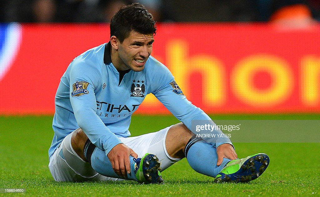 """Manchester City's Argentinian striker Sergio Aguero reacts after picking up an injury during the English Premier League football match between Manchester City and Stoke City at The Etihad stadium in Manchester, north-west England on January 1, 2013. USE. No use with unauthorized audio, video, data, fixture lists, club/league logos or """"live"""" services. Online in-match use limited to 45 images, no video emulation. No use in betting, games or single club/league/player publications."""