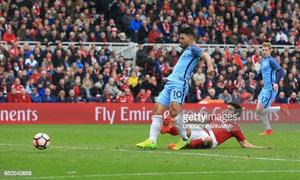 Manchester City's Argentinian striker Sergio Aguero shoots to score their second goal under pressure from Middlesbrough's Brazilian defender Fabio...