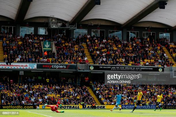 Manchester City's Argentinian striker Sergio Aguero watches the ball after shooting past Watford's Brazilian goalkeeper Heurelho Gomes to scores his...