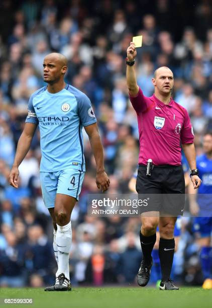 Manchester City's Belgian defender Vincent Kompany is shown a yellow card by English referee Robert Madley during the English Premier League football...
