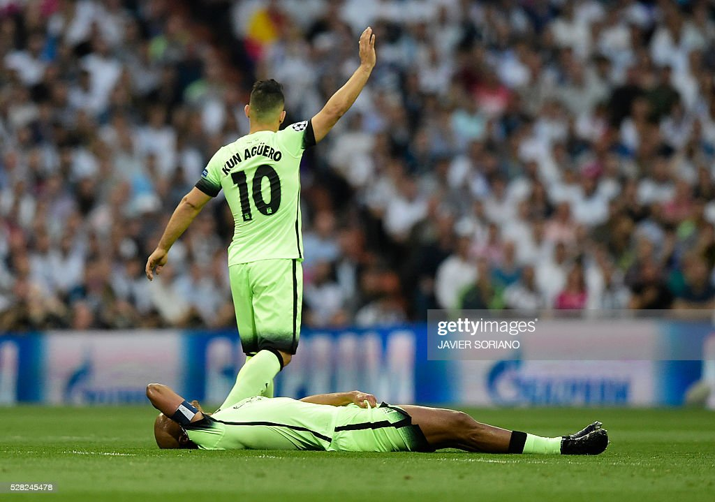 Manchester City's Belgian defender Vincent Kompany lies on the field as Manchester City's Argentinian forward Sergio Aguero (top) gestures during the UEFA Champions League semi-final second leg football match Real Madrid CF vs Manchester City FC at the Santiago Bernabeu stadium in Madrid, on May 4, 2016. / AFP / JAVIER