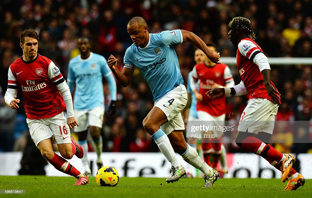 Manchester City's Belgian defender Vincent Kompany (C) runs with the ball between Arsenal's Welsh midfielder Aaron Ramsey (L) and Arsenal's French defender Bacary Sagna (R) during the English Premier League football match between Manchester City and Arsenal at the Etihad Stadium in Manchester, northwest England, on December 14, 2013. USE. No use with unauthorized audio, video, data, fixture lists, club/league logos or live services. Online in-match use limited to 45 images, no video emulation. No use in betting, games or single club/league/player publications.