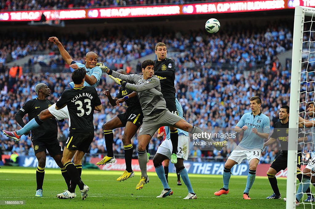 Manchester City's Belgian defender Vincent Kompany (L), Wigan Athletic's Spanish goalkeeper Joel Robles (C) and Wigan Athletic's Scottish midfielder James McArthur (R) watch as the ball bobbles over the bar for a goal kick after a corner during the English FA Cup final football match between Manchester City and Wigan Athletic at Wembley Stadium in London on May 11, 2013. AFP PHOTO / ANDREW YATES USE