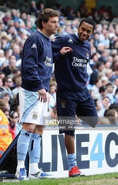Manchester City's Blumer Elano and De Souza Robinho warm up on the touchline