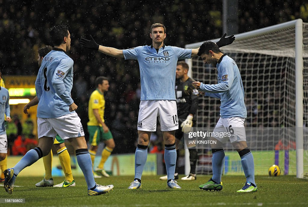 "Manchester City's Bosnian striker Edin Dzeko (C), French midfielder Samir Nasri (L) and Argentinian striker Sergio Aguero (R) celebrate after Dzeko scores his and Manchester City's second goal during the English Premier League football match between Norwich City and Manchester City at Carrow Road stadium in Norwich, England on December 29, 2012. USE. No use with unauthorized audio, video, data, fixture lists, club/league logos or ""live"" services. Online in-match use limited to 45 images, no video emulation. No use in betting, games or single club/league/player publications."