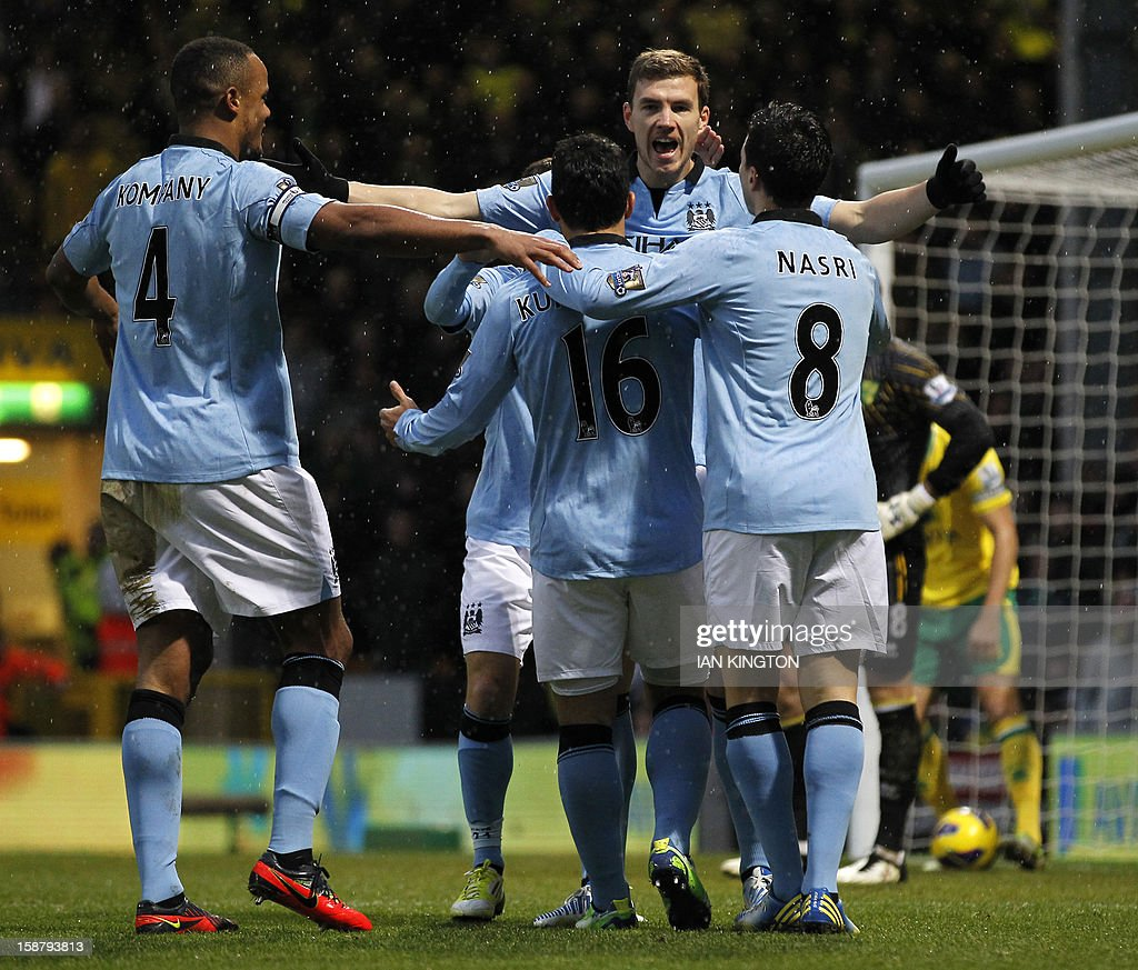 "Manchester City's Bosnian striker Edin Dzeko (2nd R), French midfielder Samir Nasri (R), Belgian defender Vincent Kompany (L) and Argentinian striker Sergio Aguero (3rd R) celebrate after Dzeko scores his and Manchester City's second goal during the English Premier League football match between Norwich City and Manchester City at Carrow Road stadium in Norwich, England on December 29, 2012. AFP PHOTO/IAN KINGTON USE. No use with unauthorized audio, video, data, fixture lists, club/league logos or ""live"" services. Online in-match use limited to 45 images, no video emulation. No use in betting, games or single club/league/player publications."