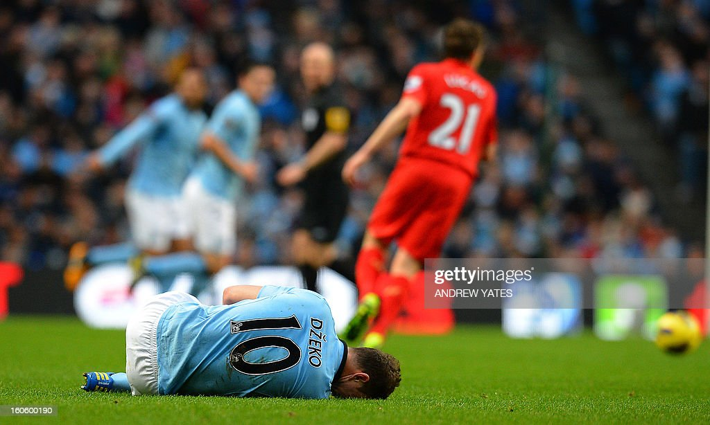 "Manchester City's Bosnian striker Edin Dzeko lies injured as Liverpool go down the field to score during the English Premier League football match between Manchester City and Liverpool at The Etihad stadium in Manchester, north-west England on February 3, 2013. USE. No use with unauthorized audio, video, data, fixture lists, club/league logos or ""live"" services. Online in-match use limited to 45 images, no video emulation. No use in betting, games or single club/league/player publications."