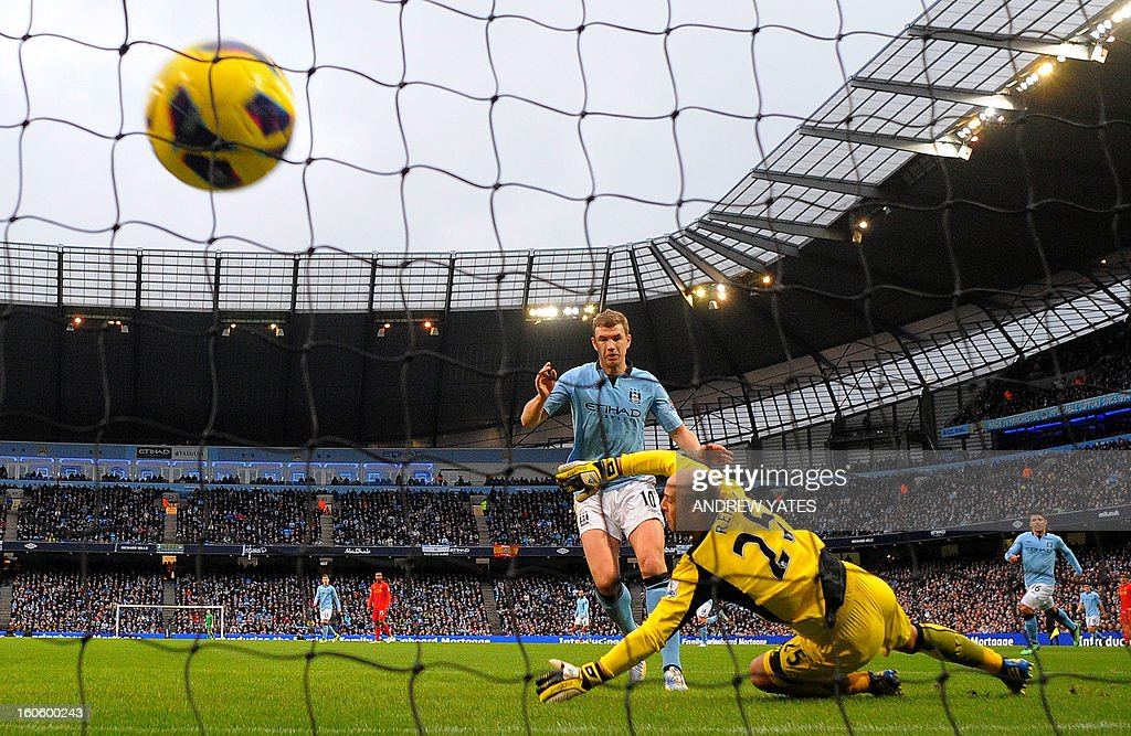 "Manchester City's Bosnian striker Edin Dzeko (C) scores the opening goal past Liverpool's Spanish goalkeeper Pepe Reina (R) during the English Premier League football match between Manchester City and Liverpool at The Etihad stadium in Manchester, north-west England on February 3, 2013. USE. No use with unauthorized audio, video, data, fixture lists, club/league logos or ""live"" services. Online in-match use limited to 45 images, no video emulation. No use in betting, games or single club/league/player publications."