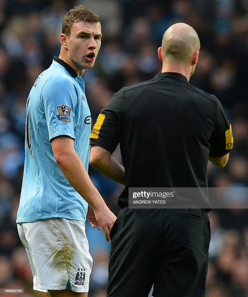 """Manchester City's Bosnian striker Edin Dzeko (L) shouts at the referee Anthony Taylor after thinking he was fouled in the build up to the Liverpool goal during the English Premier League football match between Manchester City and Liverpool at The Etihad stadium in Manchester, north-west England on February 3, 2013. USE. No use with unauthorized audio, video, data, fixture lists, club/league logos or """"live"""" services. Online in-match use limited to 45 images, no video emulation. No use in betting, games or single club/league/player publications."""