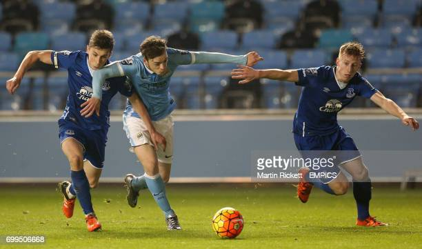 Manchester City's Brandon Barker battles for the ball with Everton's Joe Williams and Harry Charsley