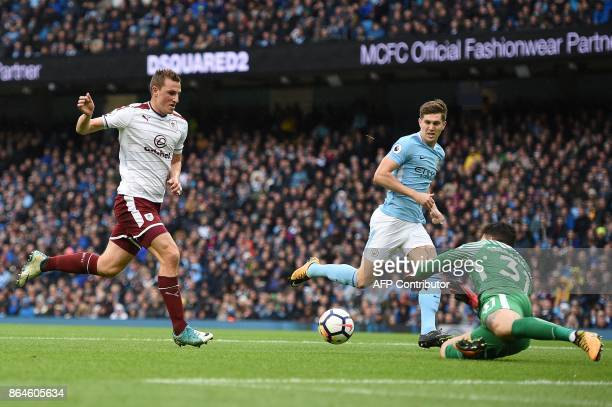 Manchester City's Brazilian goalkeeper Ederson dives to intercept the ball from the path of Burnley's New Zealand striker Chris Wood during the...