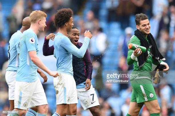 Manchester City's Brazilian goalkeeper Ederson sprays water on Manchester City's English midfielder Raheem Sterling after the English Premier League...