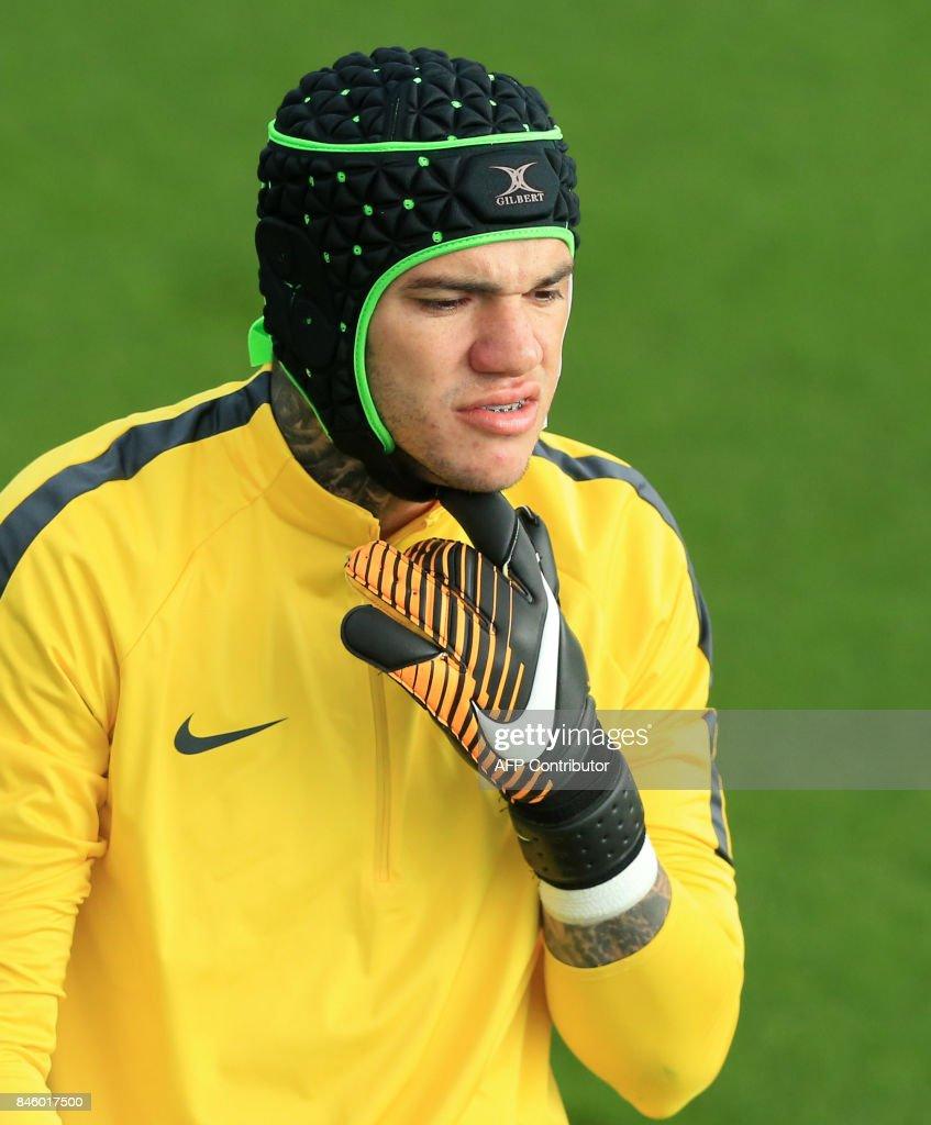 Manchester City s Brazilian goalkeeper Ederson wears head and face