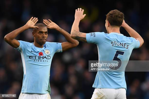 Manchester City's Brazilian midfielder Fernandinho and Manchester City's English defender John Stones celebrate following the English Premier League...