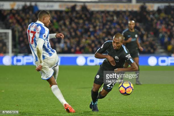 Manchester City's Brazilian midfielder Fernandinho is booked for simulation after appearing to be fouled by Huddersfield Town's Dutch midfielder...