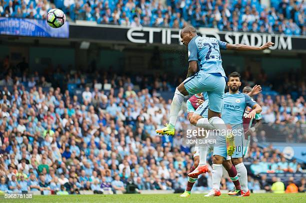 TOPSHOT Manchester City's Brazilian midfielder Fernandinho jumps to score their second goal from this header during the English Premier League...