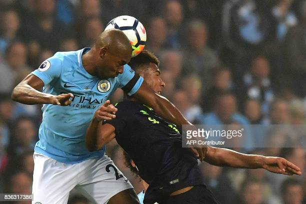 Manchester City's Brazilian midfielder Fernandinho vies with Everton's English defender Mason Holgate during the English Premier League football...