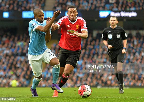 Manchester City's Brazilian midfielder Fernandinho vies with Manchester United's French striker Anthony Martial during the English Premier League...