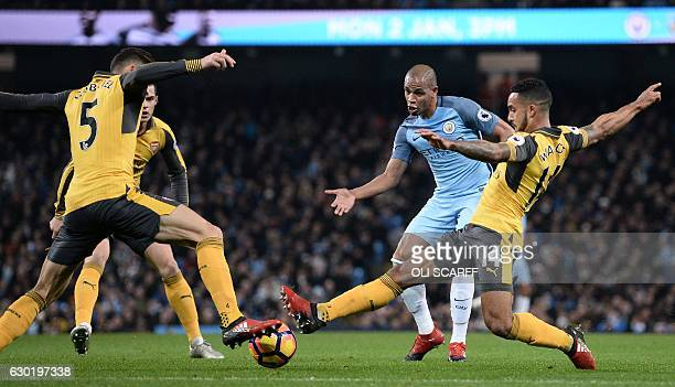 Manchester City's Brazilian midfielder Fernando vies with Arsenal's Brazilian defender Gabriel and Arsenal's English midfielder Theo Walcott during...