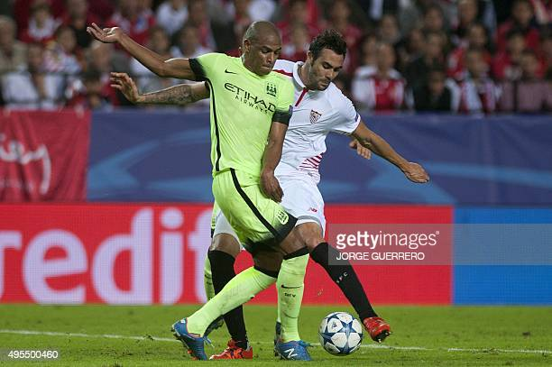 Manchester City's Brazilian midfielder Fernando vies with Sevilla's midfielder Vicente Iborra during the UEFA Champions League football match Sevilla...