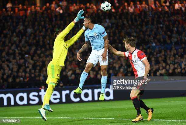 Manchester City's Brazilian striker Gabriel Jesus jumps for the ball with with Feyenoord's Australian goalkeeper Brad Jones during the UEFA Champions...