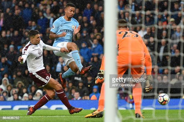 Manchester City's Brazilian striker Gabriel Jesus jumps to avoid a challenge from Burnley's English defender Matthew Lowton during the English...