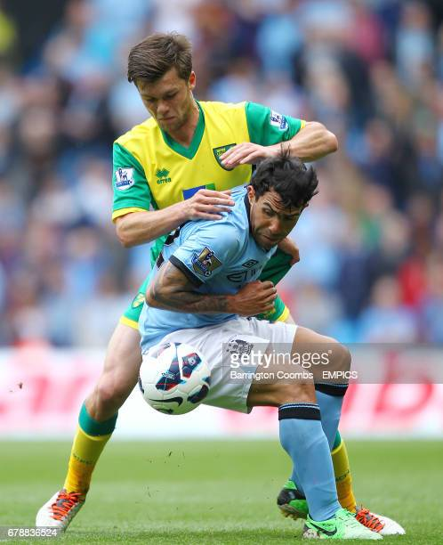 Manchester City's Carlos Tevez and Norwich City's Jonny Howson in action