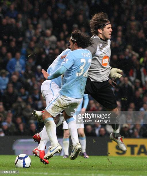 Manchester City's Carlos Tevez takes the ball from Wigan Athletic goalkeeper Vladimir Stojkovic to score his sides first goal of the game