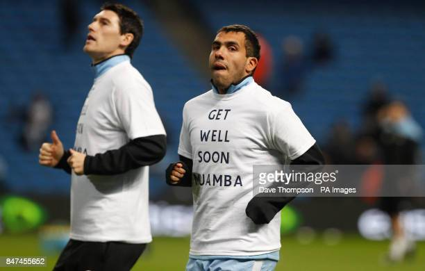 Manchester City's Carlos Tevez warms up wearing a 'Get well soon Muamba' tshirt during the Barclays Premier League match at the Etihad Stadium...