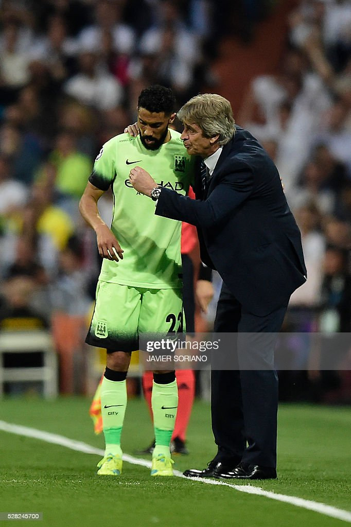Manchester City's Chilean coach Manuel Pellegrini (R) gives instructions to Manchester City's French defender Gael Clichy during the UEFA Champions League semi-final second leg football match Real Madrid CF vs Manchester City FC at the Santiago Bernabeu stadium in Madrid, on May 4, 2016. / AFP / JAVIER
