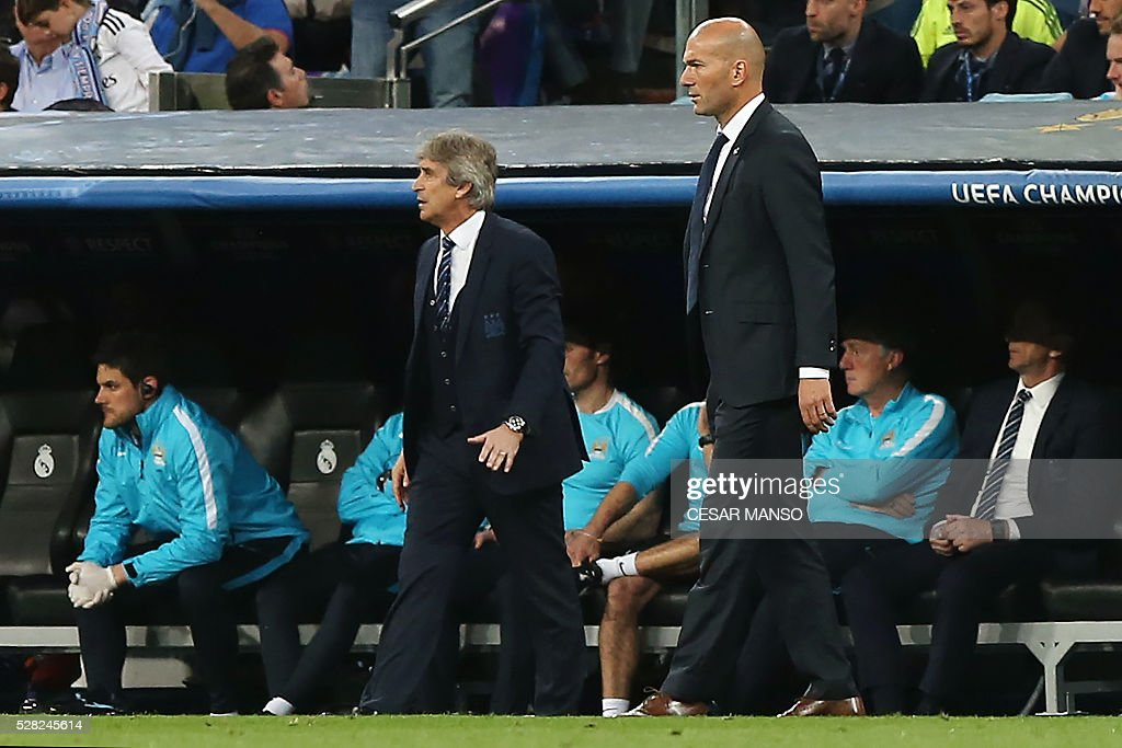 Manchester City's Chilean manager Manuel Pellegrini (L) stands past Real Madrid's French coach Zinedine Zidane during the UEFA Champions League semi-final second leg football match Real Madrid CF vs Manchester City FC at the Santiago Bernabeu stadium in Madrid, on May 4, 2016. / AFP / CESAR