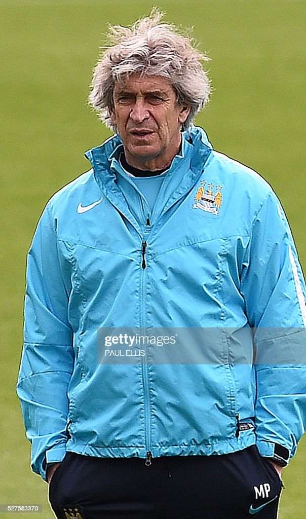 Manchester City's Chilean manager Manuel Pellegrini watches his players during a team training session at the City Academy in Manchester, north west England, on May 3, 2016. Manchester City will play against Real Madrid CF in a UEFA Champions League semi-final second leg football match in Madrid on May 4. / AFP / PAUL