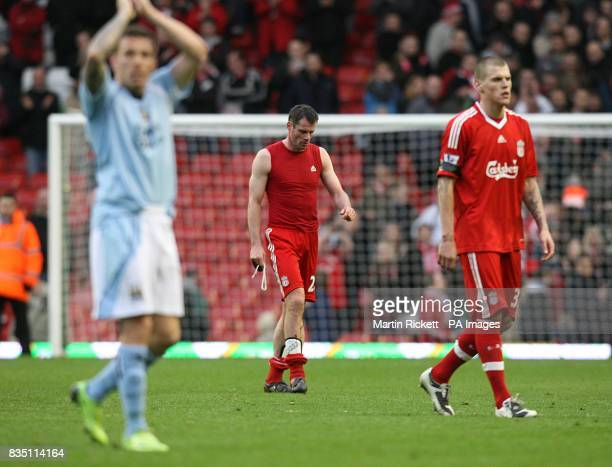 Manchester City's Craig bellamy applauds the fans as Liverpool's Jamie Carragher and Martin Skrtel walk away dejected after the final whistle