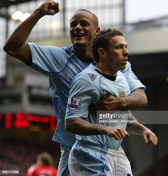 Manchester City's Craig Bellamy celebrates with team mate Vincent Kompany after his shot on goal leads to Liverpool's Alvaro Arbeloa scoring an own...