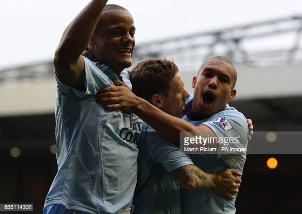 Manchester City's Craig Bellamy celebrates with team mates Vincent Kompany and Nigel De Jong after his shot on goal leads to Liverpool's Alvaro...