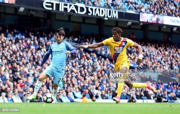 Manchester City's David Silva and Crystal Palace's Wilfried Zaha battle for the ball
