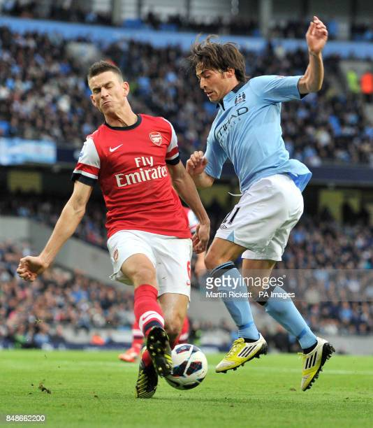 Manchester City's David Silva battles for the ball with Arsenal's Laurent Koscielny during the Barclays Premier League match at the Etihad Stadium...