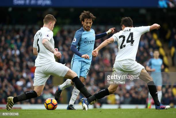 Manchester City's David Silva in action with Swansea City's Alfie Mawson and Jack Cork