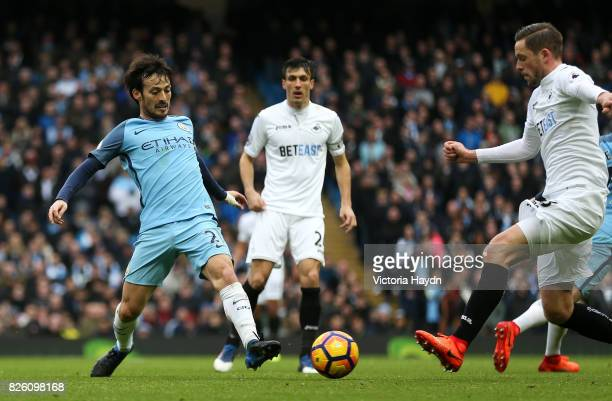 Manchester City's David Silva in action with Swansea City's Gylfi Sigurdsson
