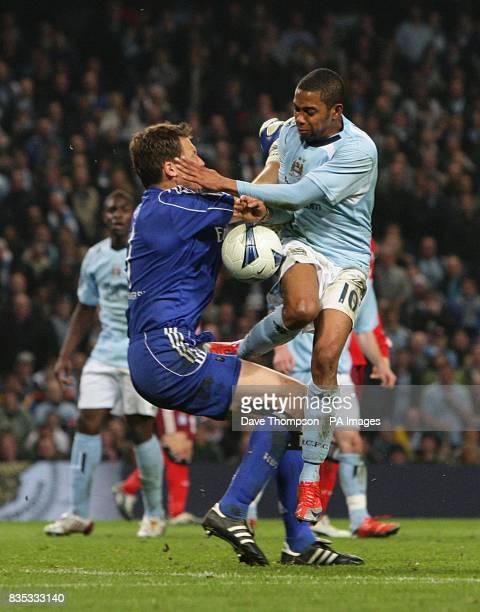 Manchester City's De Souza Robinho battles for the ball with Hamburg goalkeeper Frank Rost