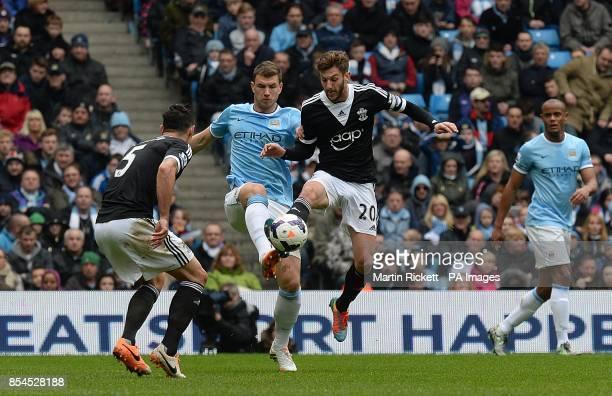 Manchester City's Edin Dzeko and Southampton's Adam Lallana battle for the ball