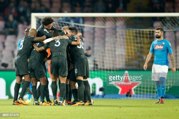 Manchester City's English defender John Stones celebrates with teammates after scoring as Napoli's defender from Albania Elseid Hysaj looks on during...
