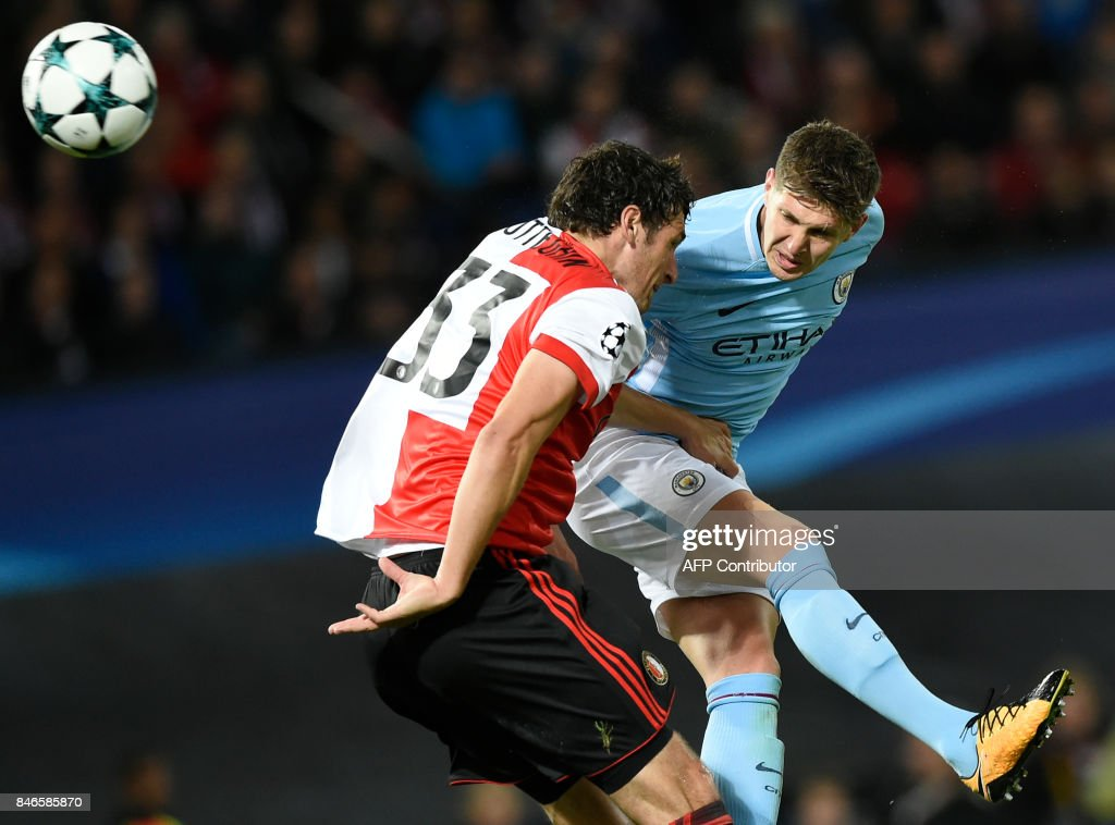 Manchester City's English defender John Stones (C) heads the ball and scores a goal during the UEFA Champions League Group F football match between Feyenoord Rotterdam and Manchester City at the Feyenoord Stadium in Rotterdam, on September 13, 2017. /